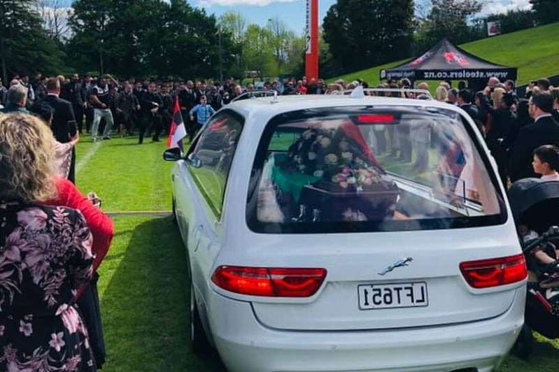 a group of people standing in front of a car: Mourners perform a second haka at the end of the funeral service