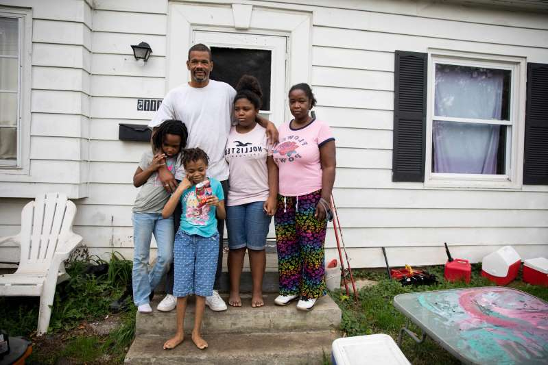 a man and a woman standing in front of a window: Kaneadsha Jones and her family stand outside of their home in Columbus, Ohio. Jones quit her job at a call center in March after she says her bosses would not let employees wear masks in the office.