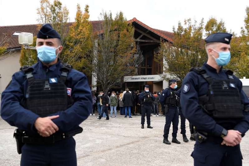 a man wearing a military uniform: French police officers at the entrance of a middle school in Conflans Saint-Honorine, 30kms northwest of Paris, on October 17, 2020. A teacher there was decapitated by an attacker who has been shot dead by policemen.