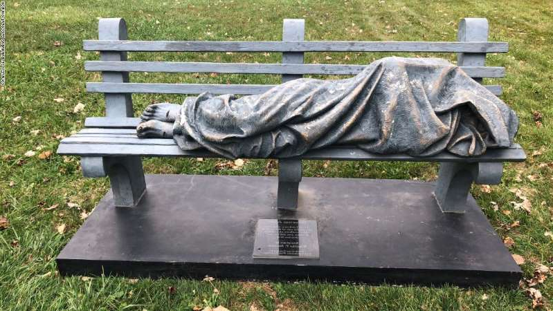 a wooden park bench sitting in the grass: Someone called the police after seeing the