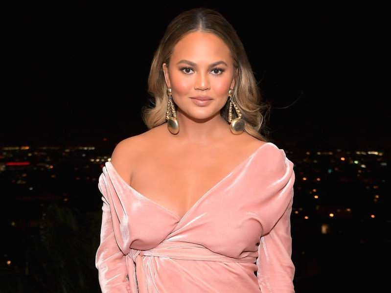 Chrissy Teigen wearing a pink dress: Chrissy Teigen attends a GQ party in 2017. Charley Gallay/Getty Images for GQ