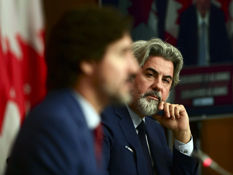 "Pablo Rodríguez wearing a suit and tie talking on a cell phone: Liberal House Leader Pablo Rodriguez with Prime Minister Justin Trudeau during a press conference in Ottawa on Friday, Oct. 16, 2020. Rodriguez called the new Conservative motion on the WE Charity scandal ""extremely partisan and irresponsible."""
