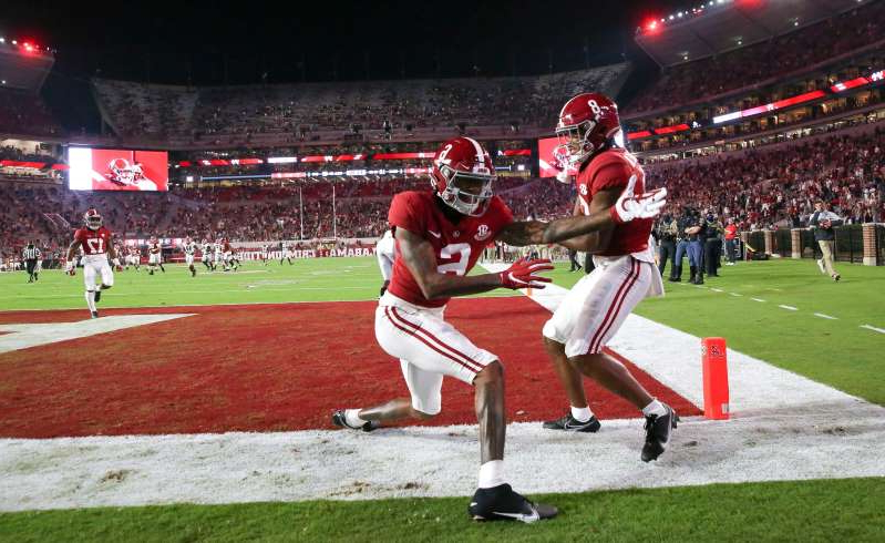 a baseball player swinging a bat at a ball: Alabama wide receivers John Metchie III and DeVonta Smith celebrate Metchie's touchdown during the first quarter at Bryant-Denny Stadium.