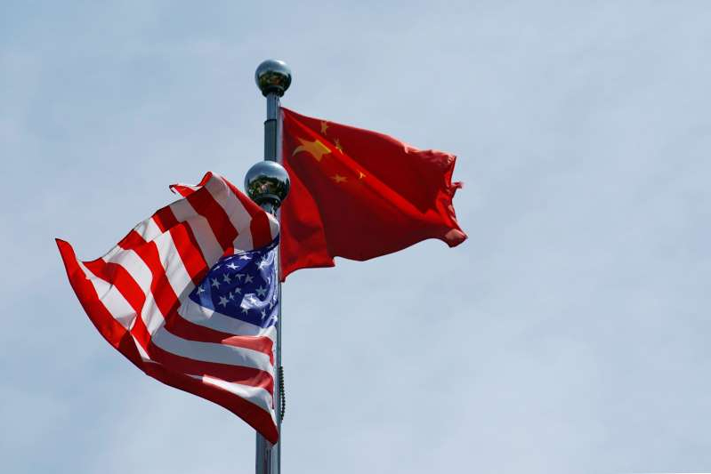 a flag flying on a cloudy day: FILE PHOTO: Chinese and U.S. flags flutter near The Bund in Shanghai