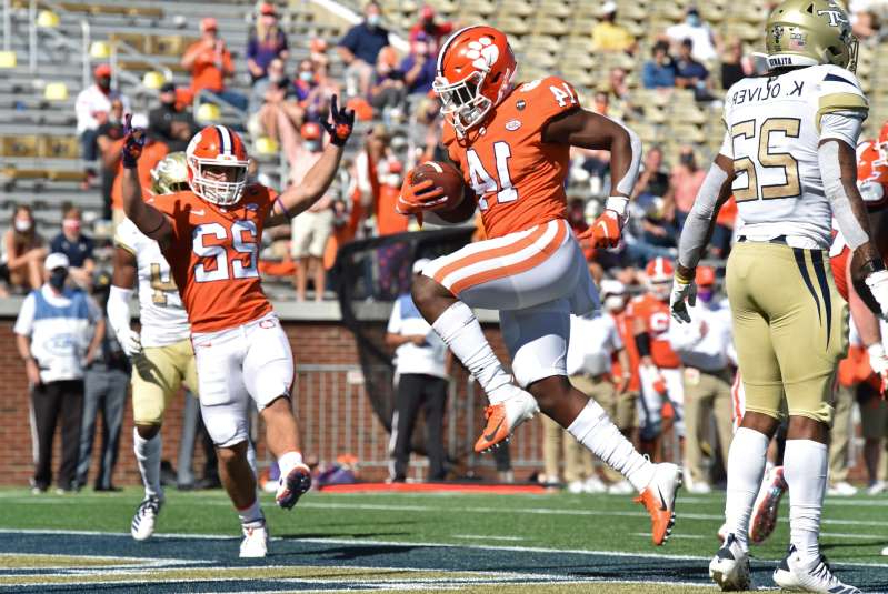 a group of men playing a game of football: Clemson running back Kobe Pace umps into the end zone for a touchdown during the first half against Georgia Tech at Bobby Dodd Stadium.