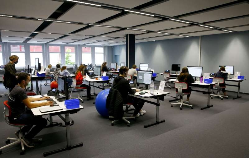 a group of people sitting at a desk in an office: FILE PHOTO: Employees work at the center for contact tracing of the Canton of Zurich in Pfaeffikon