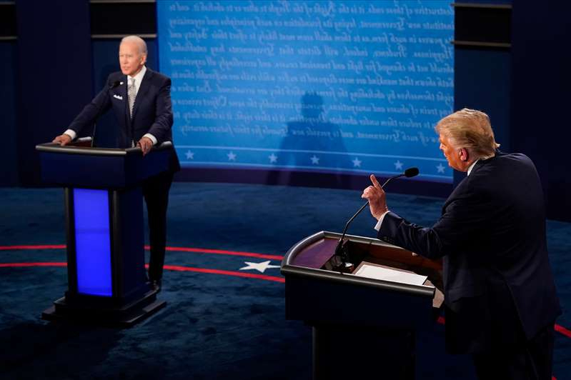 a group of people sitting at a table: President Donald Trump speaks during the first presidential debate against Joe Biden in Cleveland. They will debate again Thursday.