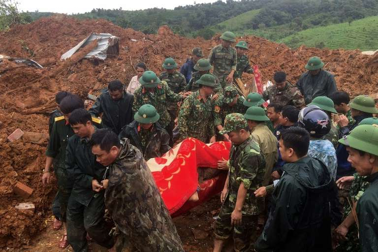 a group of people standing on a rock: Rocks rained down on the barracks of a military station in Quang Tri province, with 22 soldiers believed to have been buried underneath thick mud
