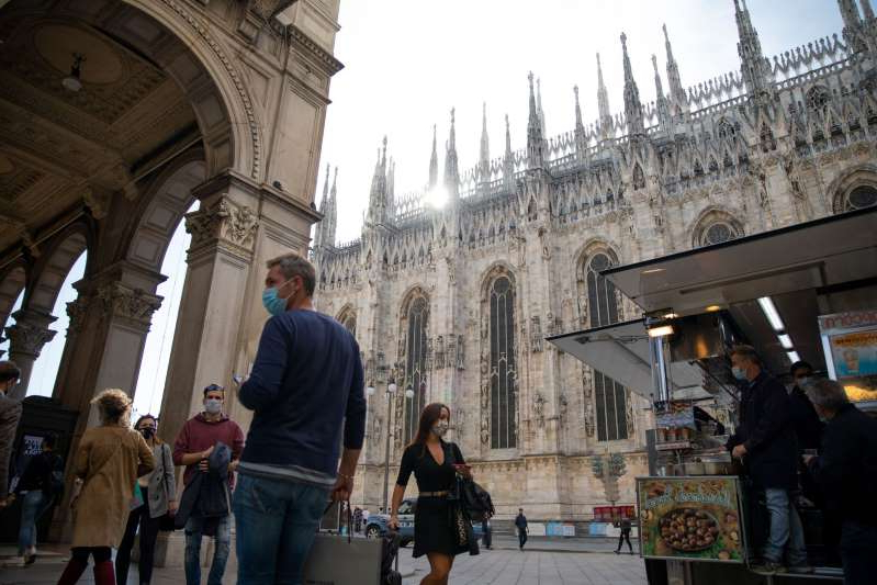 a group of people walking in front of a building: Pedestrians wearing protective face masks pass near Duomo Cathedral square in Milan, Italy, on Thursday, Oct. 8, 2020. Italy's government reinforced measures to curb the coronavirus pandemic, including decreeing that protective masks must be worn outdoors across the country.