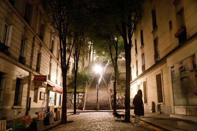 a group of people walking on a city street at night: A woman walks her dog in Montmartre during the late-night curfew due to restrictions against the spread of the coronavirus disease (COVID-19) in Paris
