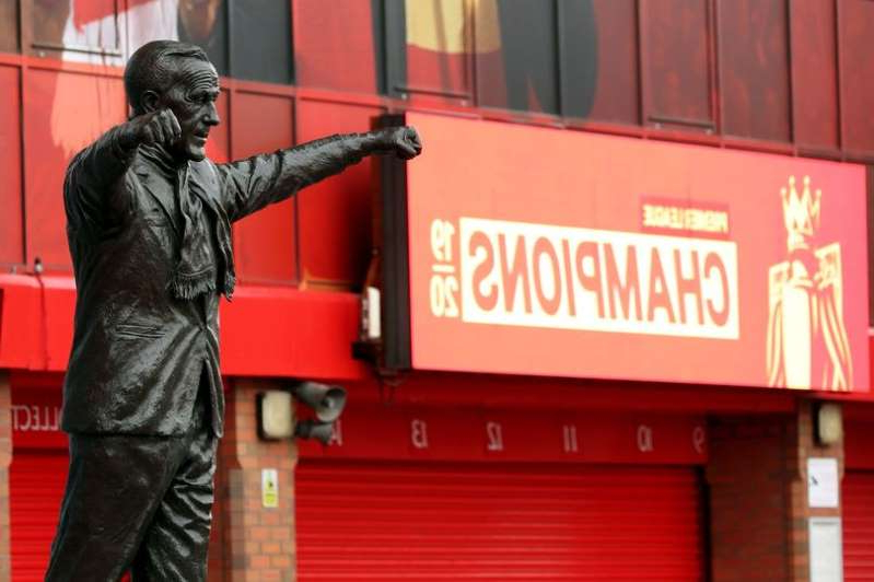 a man standing in front of a building: Bill Shankly Statue outside of Anfield Stadium.