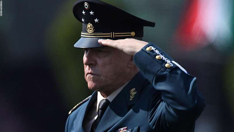 a man wearing a suit and tie: Mexico's Defense Secretary Gen. Salvador Cienfuegos Zepeda salutes soldiers at the Number 1 military camp in Mexico City.