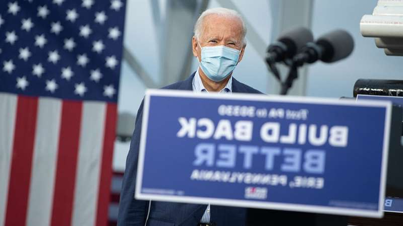 a person holding a sign: Five things to know about Biden's tax proposals