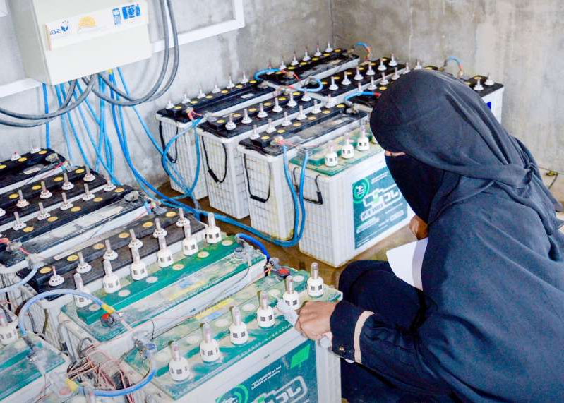 a person on the machine: A woman checks batteries at the Abs solar microgrid station [Photo courtesy of SDF YEMEN]