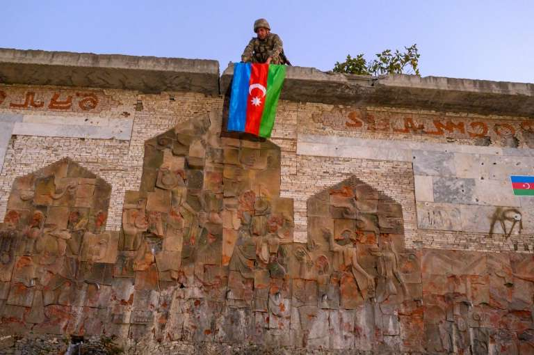 a person standing in front of a brick building: An Azeri soldier hangs the flag of Azerbaijan on a wall in Jabrayil