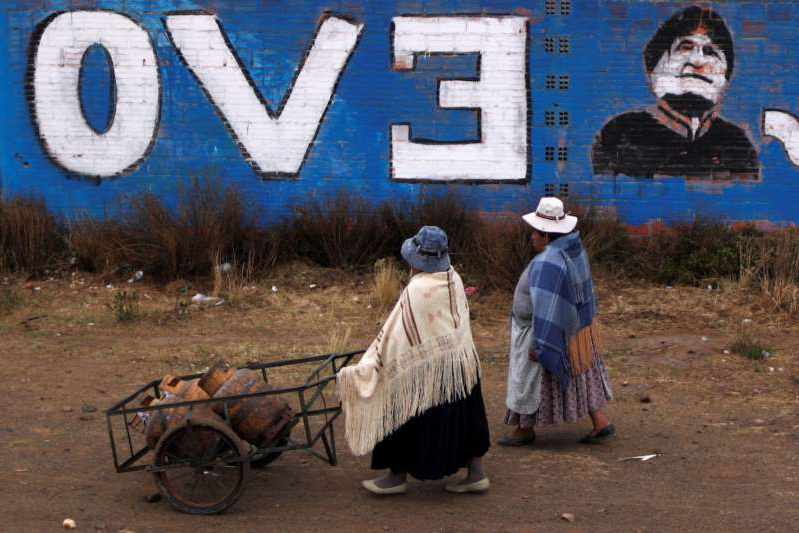 a person with graffiti on the side of the road: Women walk past a wall with a graffiti depicting former Bolivian President Evo Morales, before general elections in La Paz