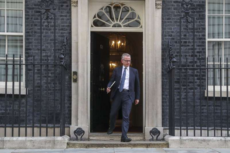 Michael Gove standing in front of a brick building with 10 Downing Street in the background: Michael Gove, U.K. Chancellor of the Duchy of Lancaster, departs from number 10 Downing Street in London, U.K., on Wednesday, July 24, 2019. Boris Johnson became prime minister Wednesday afternoon, and is preparing to announce his top ministerial team to deliver the U.K.'s exit from the European Union.