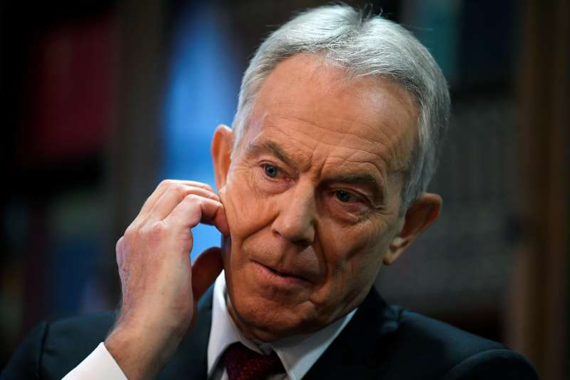 Tony Blair wearing a suit and tie talking on a cell phone: FILE PHOTO: Former British Prime Minister Tony Blair speaks at the Hallam Conference Centre in London