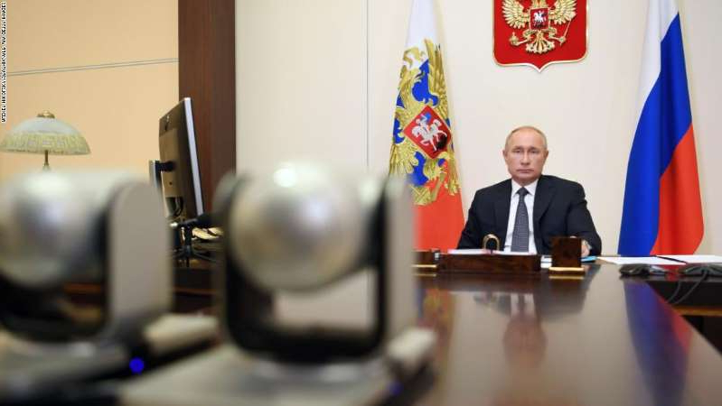 Vladimir Putin sitting at a desk: Russian President Vladimir Putin announced the vaccine on a video conference call with government officials.