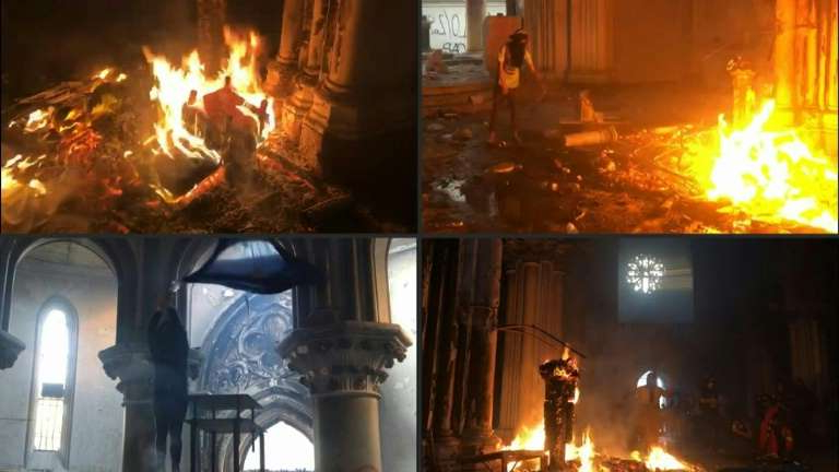 a fire place sitting in front of a fireplace: Protesters set a fire inside San Francisco de Borja church in Santiago.