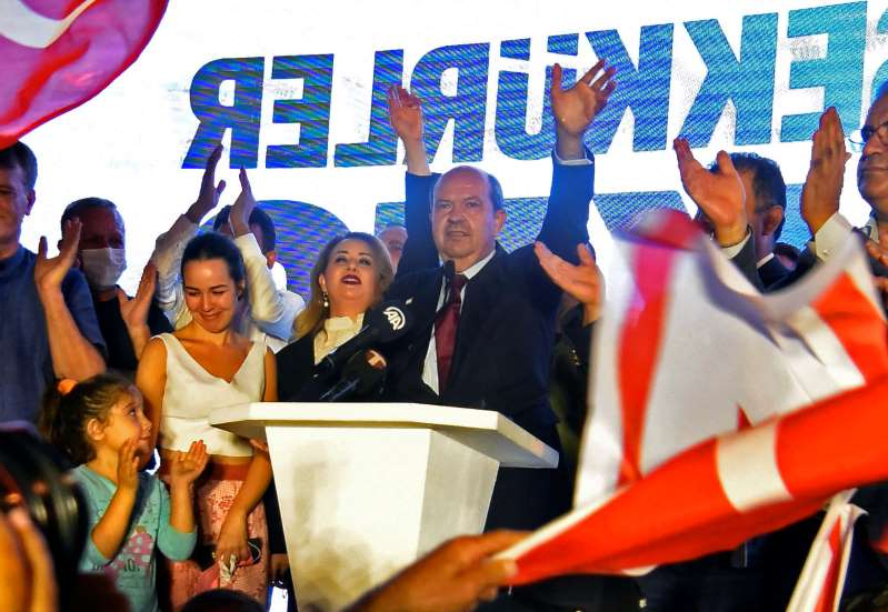 a group of people holding a sign: Turkish Cypriot politician Ersin Tatar celebrates his election victory in Turkish-controlled northern Nicosia