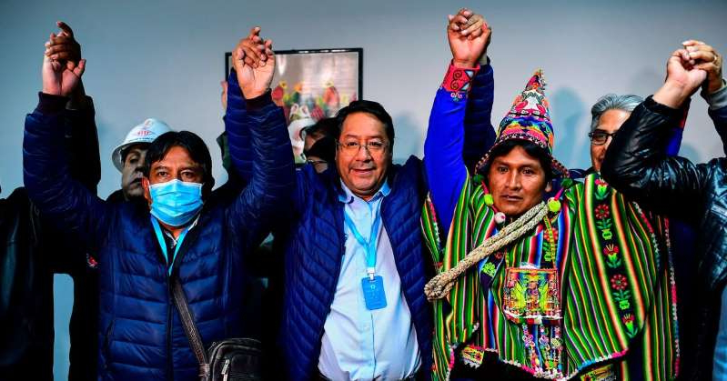 a group of people posing for the camera: Bolivia's leftist presidential candidate Luis Arce (center) of the Movement for Socialism party celebrates with running mate David Choquehuanca (right). Ronaldo Schemidt/AFP via Getty Images