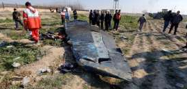 a group of people standing in the dirt: Wreckage from Flight PS752, which was shot down over Tehran on Jan. 8, killing all 176 people aboard.