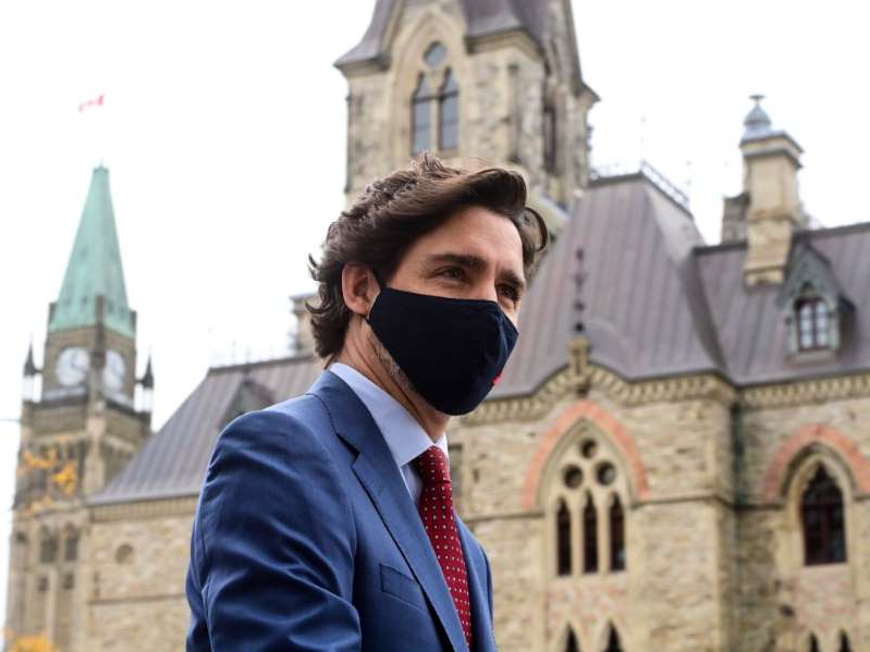 a man wearing a suit and tie standing in front of a building: Prime Minister Justin Trudeau makes his way to a press conference in Ottawa on Oct. 16.