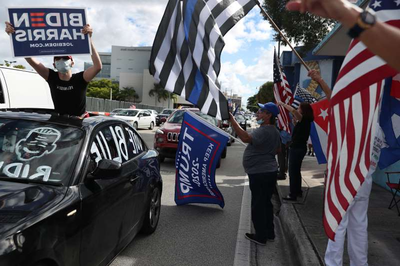 a person holding a sign: A caravan of supporters for Democratic presidential nominee Joe Biden drives past supporters of President Donald Trump standing on the sidewalk next to the Versailles Restaurant on Oct. 18, 2020 in Miami, Florida.