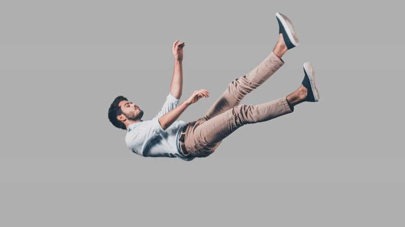 a person jumping in the air: Young male in chinos and light blue shirt falling suspended in mid-air on a grey background