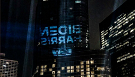 a tall building lit up at night: Steelworkers union projects giant Biden-Harris logo on Trump Tower Chicago