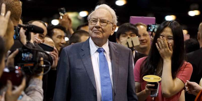 Warren Buffett standing in front of a crowd posing for the camera: Rick Wilking/Reuters
