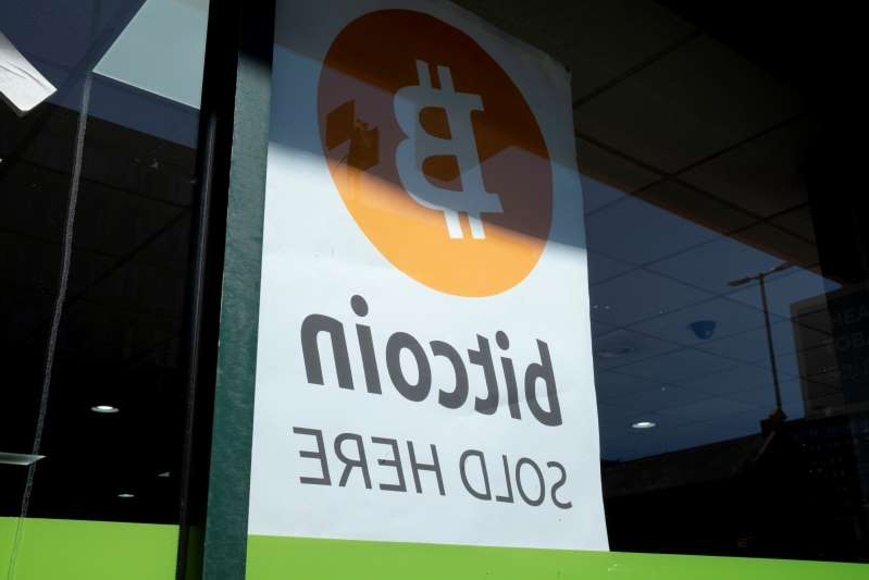 a close up of a sign: A sign advertising bitcoin in a small shop window in Birmingham, United Kingdom.