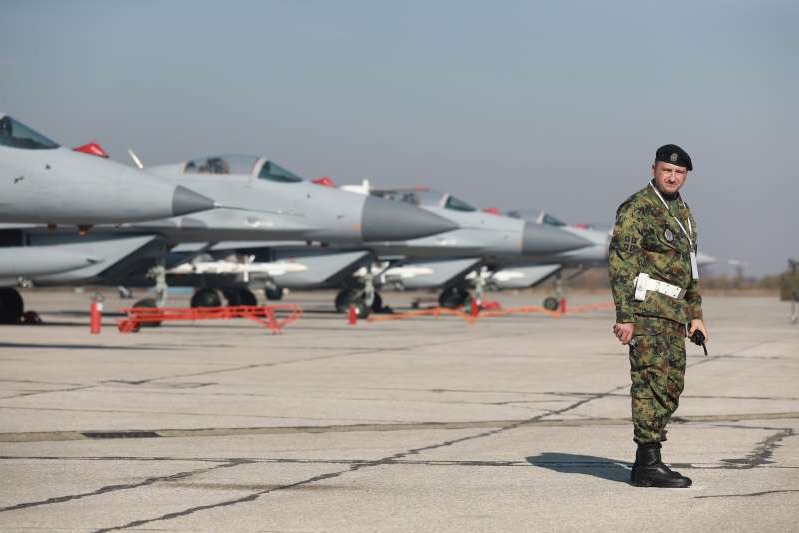 a fighter jet sitting on top of a runway: FILE PHOTO: Russian-made MiG-29 fighter jets are parked on a runway during the air show at Batajnica military airfield in Belgrade, Serbia