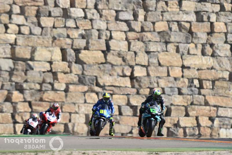 a group of people on a motorcycle in front of a brick wall: Franco Morbidelli, Petronas Yamaha SRT