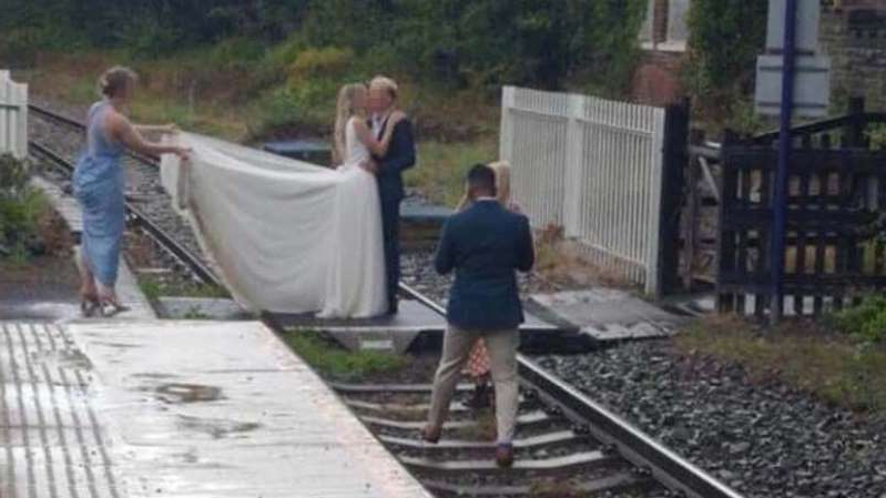 a group of people on a train track: A wedding party taking a railway photoshoot in Whitby. Pic: Network Rail