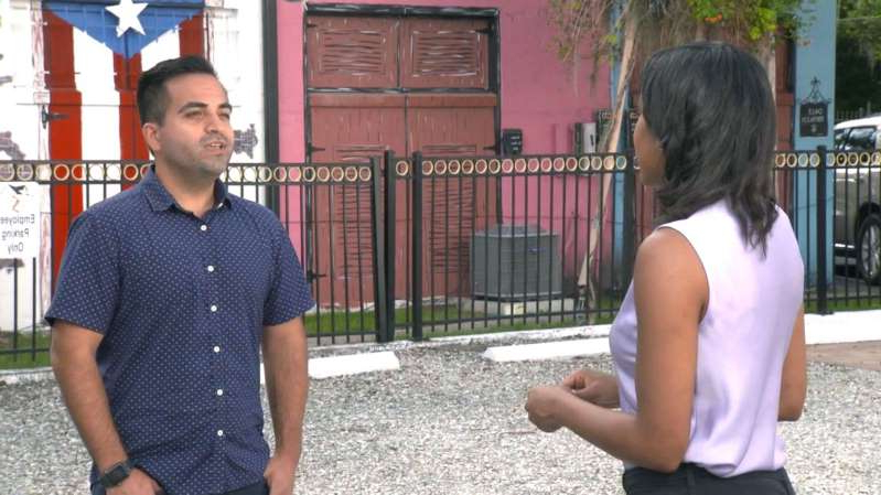 a man and a woman standing on a sidewalk: Ricardo Negron is helping Puerto Ricans navigate the Democratic process with group Latino Justice.