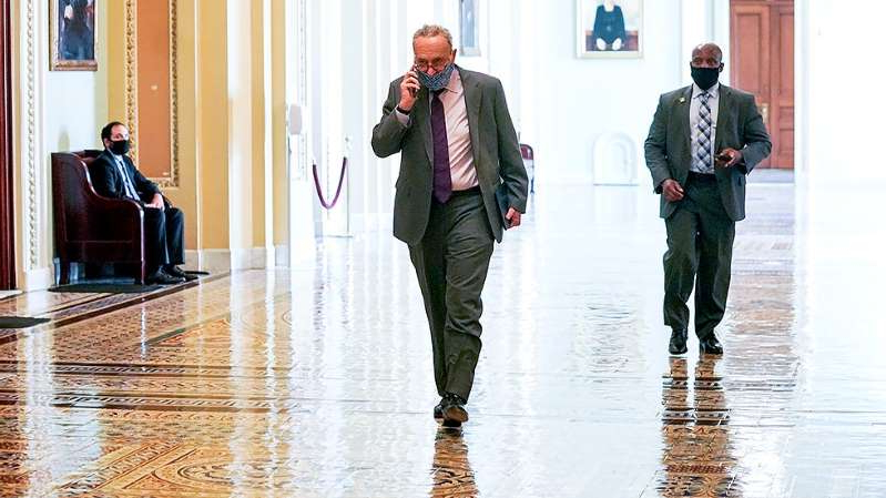 a man wearing a suit and tie talking on a cell phone: GOP blocks Schumer effort to adjourn Senate until after election