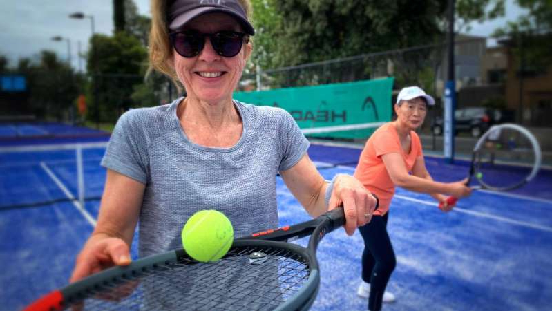 a person hitting a ball with a racket: Lilee Sampsom (left) and Sonia Sbardellotto are happy to be back on the court at the Elsternwick Tennis Club. (ABC News: Peter Drought)