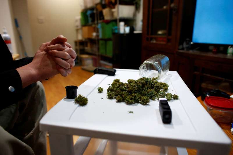 a person sitting at a table: FILE PHOTO: Mobile research lab to study effects of cannabis in Colorado