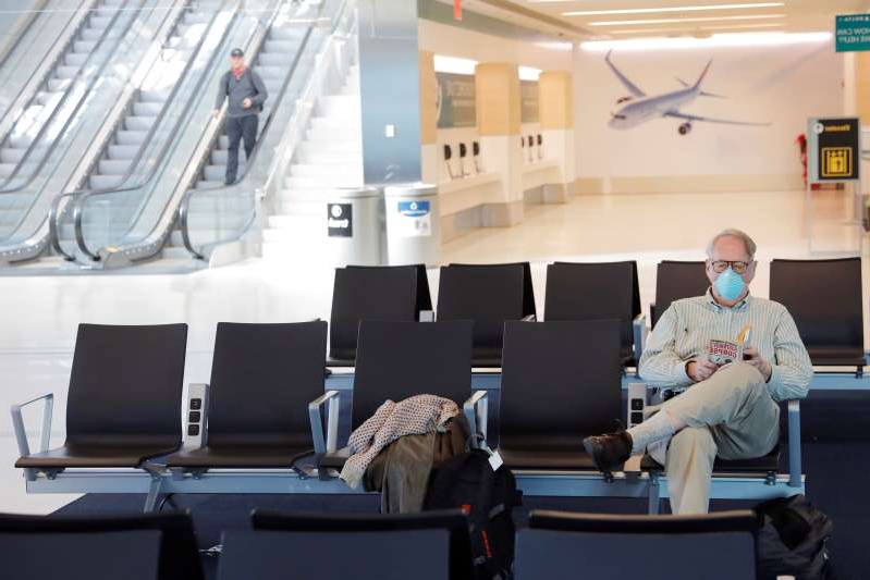 a person sitting on a couch: A traveler wears a mask while reading in John F. Kennedy International Airport in New York City. The CDC has advised that people on public conveyances — including trains, planes and buses — wear masks for the entire duration of their trip.