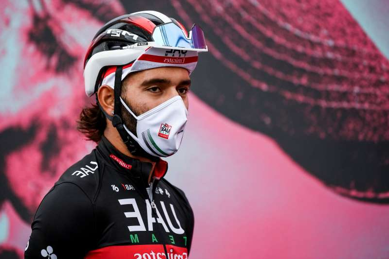 Cyclist Fernando Gaviria wears a face mask to curb the spread of COVID-19 as he attends the 13th stage of the Giro d'Italia cycling race, from Cervia to Monselice, Italy, on Friday, Oct. 16, 2020. Colombian sprinter Gaviria is the latest cyclist to test positive for the coronavirus and be withdrawn from the Giro d'Italia. Gaviria and a staff member for Team AG2R La Mondiale were the only positives out of 492 tests carried out Sunday and Monday, Oct. 19, 2020. (Marco Alpozzi/LaPresse via AP)