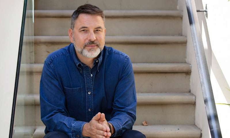 David Walliams sitting in front of a building: Hello! Magazine