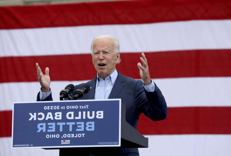 Joe Biden holding a sign: Presidential candidate Joe Biden speaks at a drive-in rally at UAW Local 14 in Toledo, Ohio, on Monday.