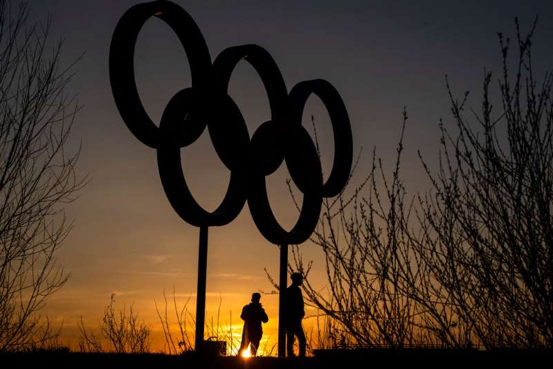 The Olympic rings are seen as sunset in the Olympic Park in Stratford on March 23, 2020 in London, England.