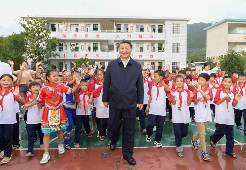 Xi Jinping et al. standing in front of a crowd posing for the camera: Xi Jinping at a primary school in China's Hunan Province, in Sept. 2020.
