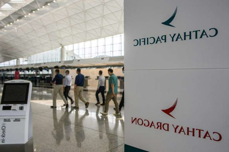 a group of people standing in front of a sign: Cathay Dragon, a subsidiary that primarily flies shorter haul flights within Asia, will cease operations