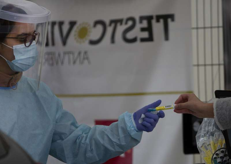 A health care worker, right, takes a vial as she prepares to administer a nose-swab test at the mobile COVID-19 testing site in Antwerp, Belgium, Tuesday, Oct. 20, 2020. Bars and restaurants across Belgium have been shut down for a month and a night-time curfew entered into force Monday, as health authorities warned of a possible sanitary