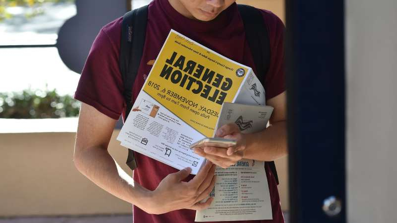a person holding a sign: Students wait in line to cast their ballot at a polling station on the campus of the University of California, Irvine, on November 6, 2018