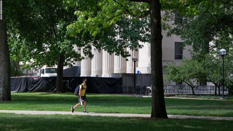 a person throwing a frisbee at the park: A student walks through the Diag on the University of Michigan campus in August. All Michigan undergraduates are now under a two-week emergency stay-at-home order.